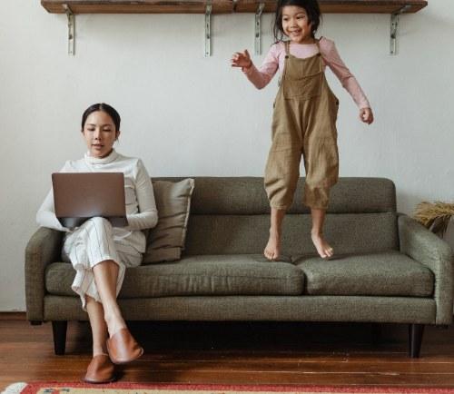 mamá trabajando en casa e hijo jugando cerca